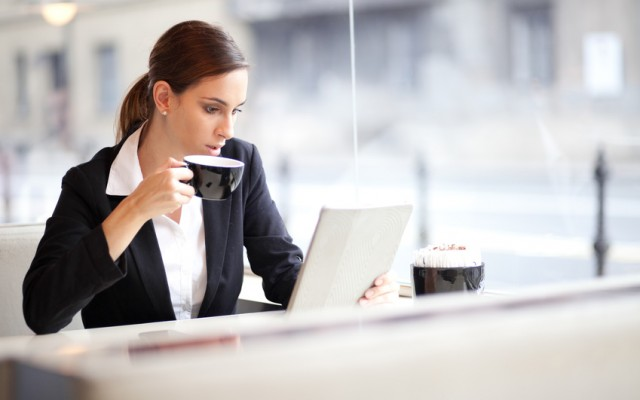 Businesswoman having a cup of coffee while reading an article on