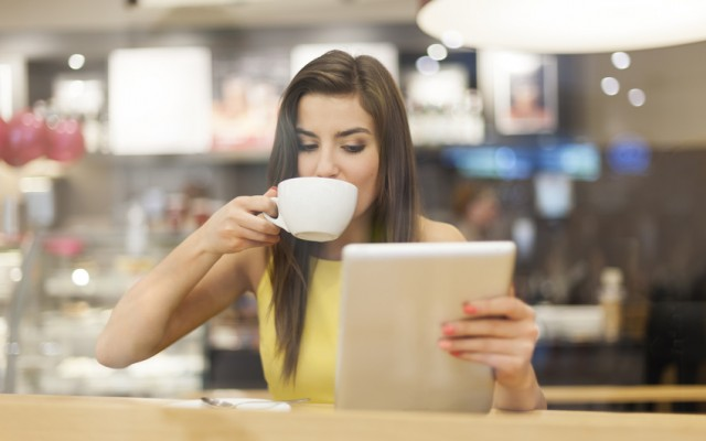 Beautiful woman in cafe using digital tablet