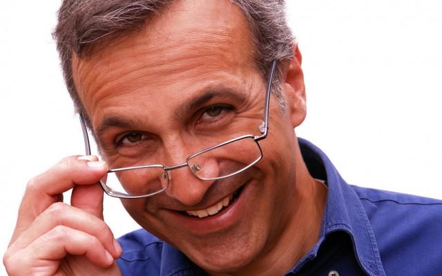 Uomo sorridente che abbassa gli occhiali con sguardo intenso