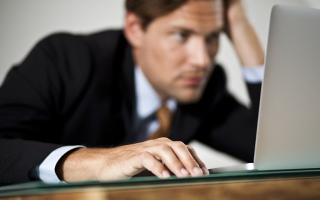 Businessman rests his head in one hand while working on laptop