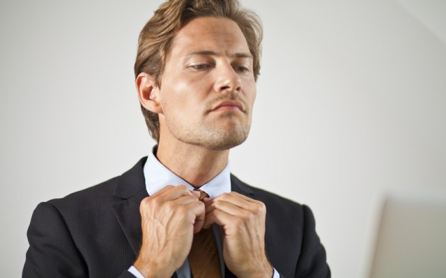 Serious businessman adjusting tie