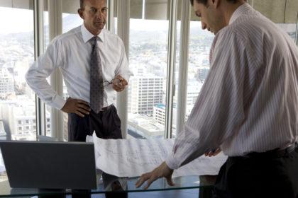 Mature businessman holding glasses by colleague looking at blueprint on desk, portrait