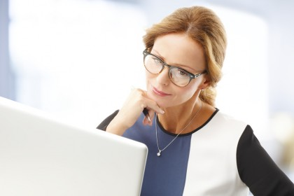 Portrait of middle age business woman with lapotop working at office.